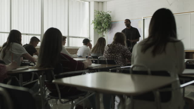 wide panning shot of teacher lecturing students in classroom / provo, utah, united states - classroom stock videos & royalty-free footage