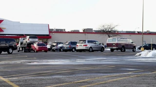a wide panning shot of the stadium plaza strip mall in jersey city new jersey on a cold winter day with piles of snow in the parking lot a tight shot... - centro commerciale suburbano video stock e b–roll