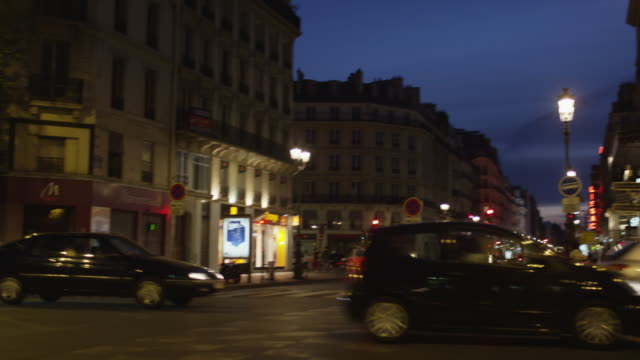 Wide panning shot of traffic on busy city street at night / Paris, France