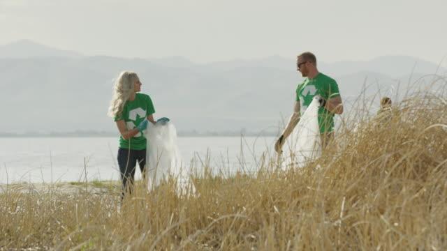 Wide panning shot of volunteers collecting garbage at lake / Vineyard, Utah, United States