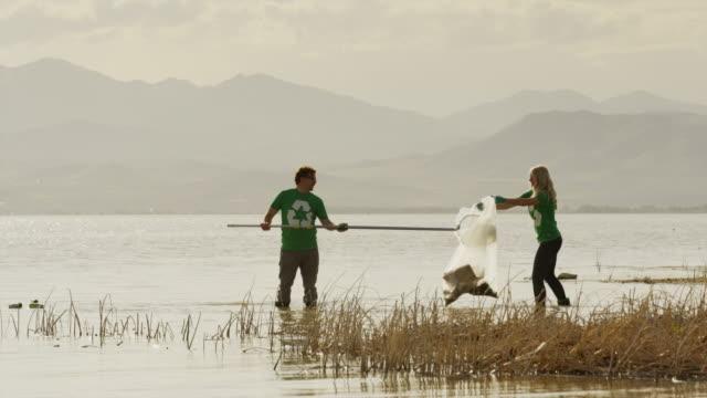 wide panning shot of volunteers scooping garbage from lake / vineyard, utah, united states - ausschöpfen stock-videos und b-roll-filmmaterial
