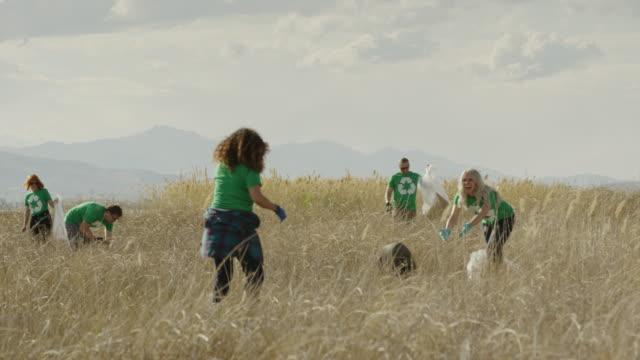 wide panning shot of volunteers throwing tire in field / vineyard, utah, united states - sozialarbeit stock-videos und b-roll-filmmaterial