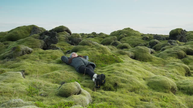 wide panning shot of woman laying in mossy landscape / iceland - legs crossed at ankle stock videos & royalty-free footage