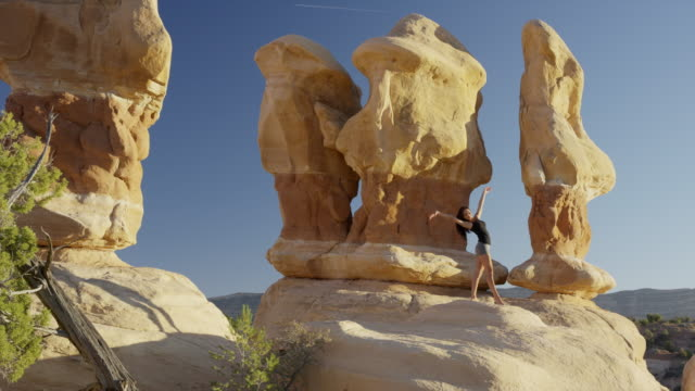 wide panning shot of woman performing yoga on rock formation / escalante, utah, united states - escalante stock-videos und b-roll-filmmaterial
