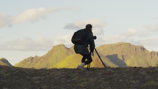 Wide panning shot of woman photographing mountain range  / Rangarvallasysla, Iceland