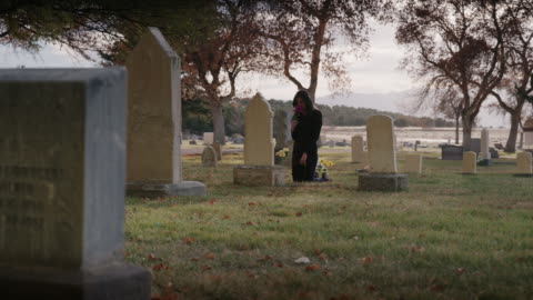 wide panning shot of woman placing bouquet on gravestone / spring city, utah, united states - death stock videos & royalty-free footage