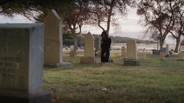 wide panning shot of woman placing bouquet on gravestone / spring city, utah, united states - trauernder stock-videos und b-roll-filmmaterial