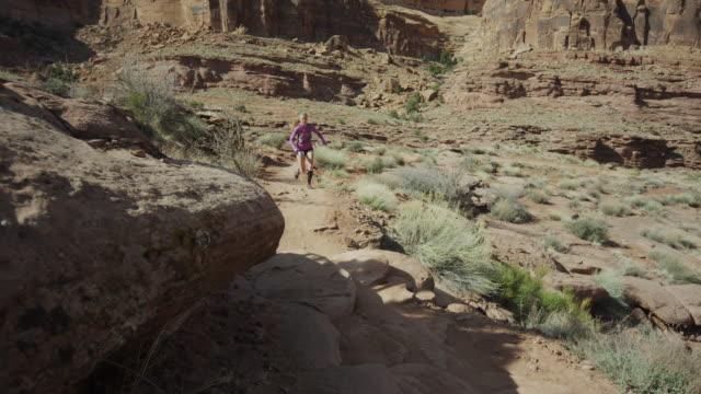 vídeos de stock, filmes e b-roll de wide panning shot of woman trail running in desert / moab, utah, united states - calções de corrida