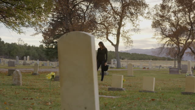 Wide panning shot of woman walking in cemetery / Spring City, Utah, United States