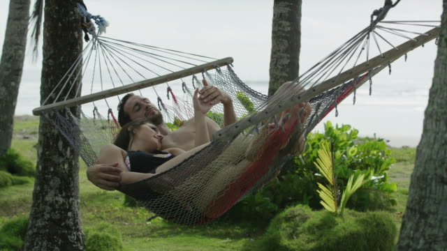 Wide panning slow motion shot of couple relaxing in hammock / Esterillos, Puntarenas, Costa Rica