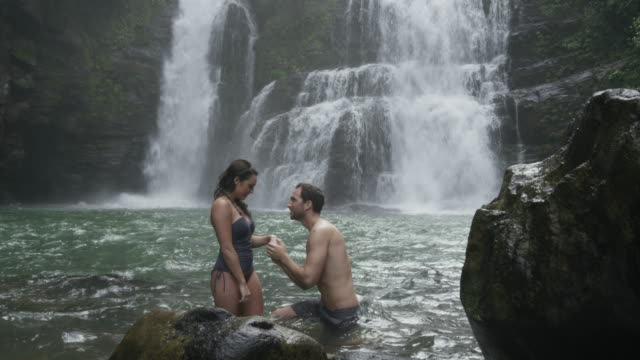 Wide panning slow motion shot of man proposing to girlfriend near waterfall / Santa Juana, Costa Rica