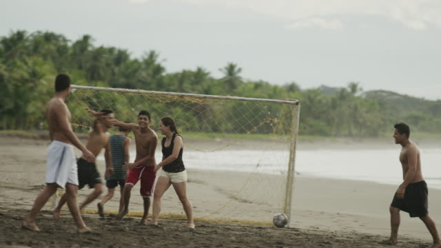 wide panning slow motion shot of people celebrating soccer goal on beach / esterillos, puntarenas, costa rica - scoring a goal stock videos and b-roll footage