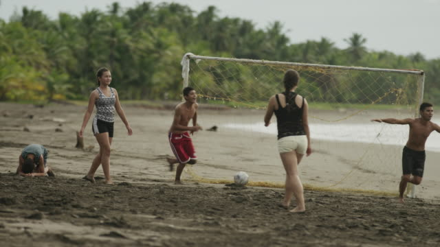 wide panning slow motion shot of people cheering and playing soccer on beach / esterillos, puntarenas, costa rica - scoring a goal stock videos and b-roll footage