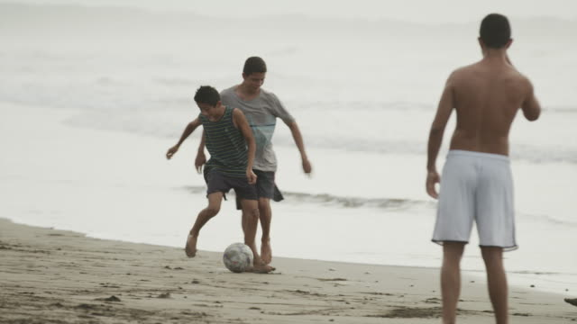 wide panning slow motion shot of people cheering and playing soccer on beach / esterillos, puntarenas, costa rica - 上半身裸点の映像素材/bロール