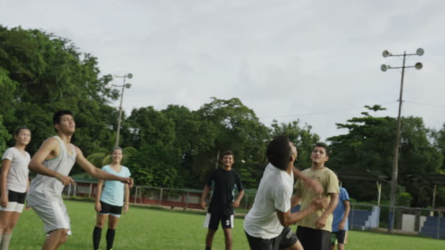 Wide panning slow motion shot of soccer team practicing on field / Esterillos, Puntarenas, Costa Rica