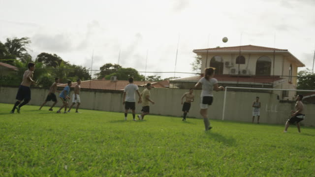 wide panning slow motion shot of soccer teams playing on field / esterillos, puntarenas, costa rica - puntarenas stock-videos und b-roll-filmmaterial