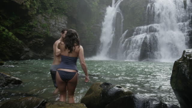 Wide panning slow motion view of couple entering swimming hole near waterfall / Santa Juana, , Costa Rica