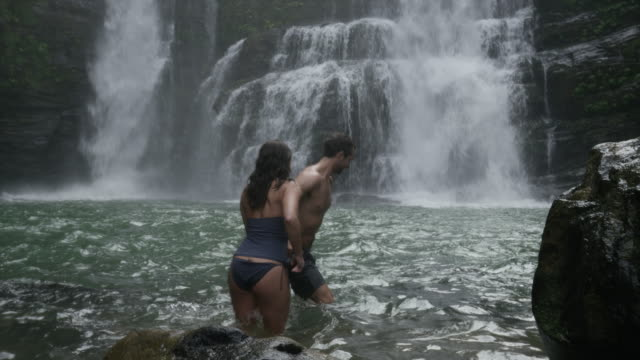 wide panning slow motion view of couple in swimming hole near waterfall / santa juana, , costa rica - costa rica stock-videos und b-roll-filmmaterial