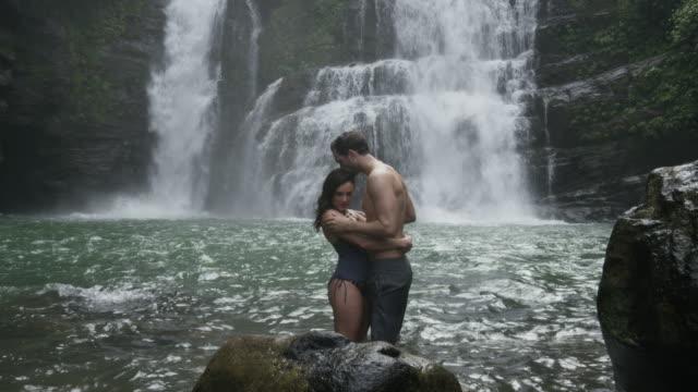 wide panning slow motion view of couple kissing in swimming hole near waterfall / santa juana, , costa rica - badbyxor bildbanksvideor och videomaterial från bakom kulisserna