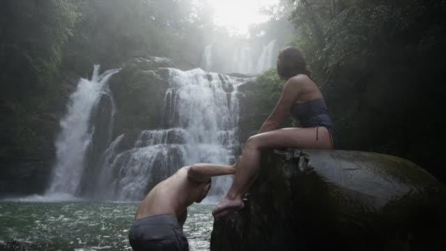 wide panning slow motion view of couple swimming near waterfall / santa juana, , costa rica - badbyxor bildbanksvideor och videomaterial från bakom kulisserna