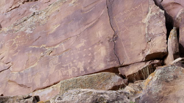 vídeos de stock e filmes b-roll de wide panning view of petroglyphs on cliff in nine mile canyon - anasazi