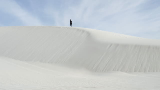 wide, person walks alone on desert dunes - spärlichkeit stock-videos und b-roll-filmmaterial