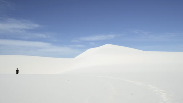 wide, person wanders in desert - abgeschiedenheit stock-videos und b-roll-filmmaterial