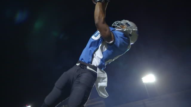 ms slo mo. wide receiver jumps to catch football and falls into end zone for touchdown under stadium lights. - fangen stock-videos und b-roll-filmmaterial