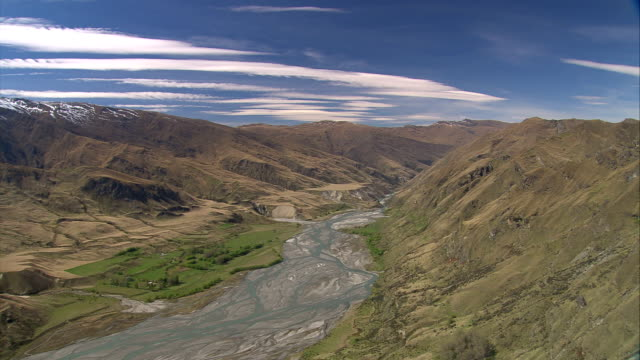 a wide river flows past rolling hills. available in hd. - eroded stock videos & royalty-free footage