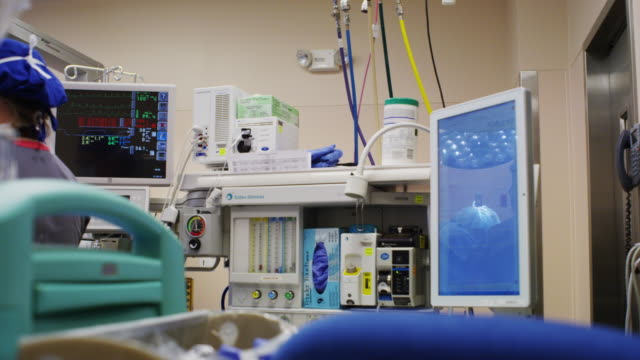 Wide scene of EKG and gowned surgeon and nurse reflected in a computer monitor during a surgical procedure in a hospital operating room.