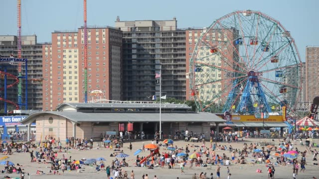 a wide scenic shot of a crowded beach cyclone wonder wheel and housing projects on a clear sunny day in coney island new york a wide scenic shot of a... - coney island brooklyn stock videos & royalty-free footage