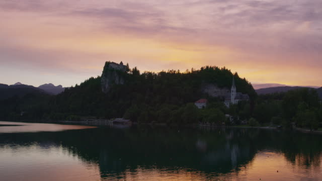 Wide scenic view of lake waterfront at sunset / Bled, Slovenia