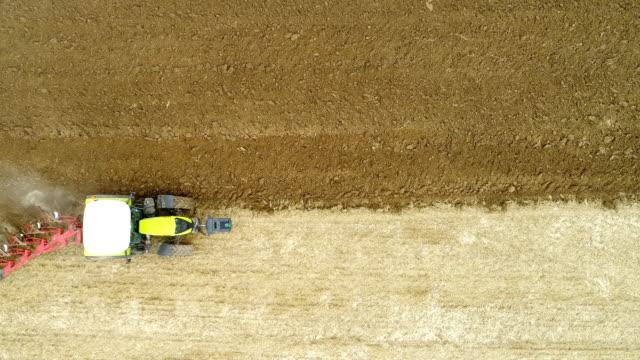 Wide shoot of tractor plowing field 4K