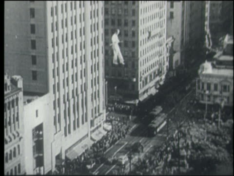 B/W wide shot 1930s/40s man balancing on tightrope above crowded city street / Los Angeles