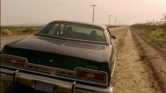 wide shot 1970s ford ltd on side of desert road pulling onto road and driving away / kicking up dust - straßenrand stock-videos und b-roll-filmmaterial