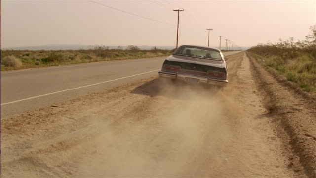 wide shot 1970s ford ltd on side of desert road pulling onto road and driving away / kicking up dust - 道ばた点の映像素材/bロール