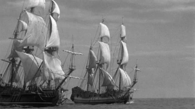 wide shot 2 galleons and small boats in wake passing by - nave a vela video stock e b–roll