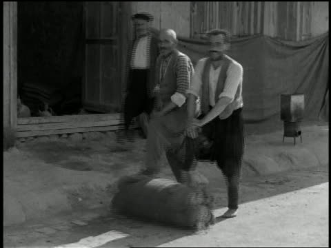 1932 wide shot 2 men rolling fabric on street with their feet - turkey middle east stock videos & royalty-free footage