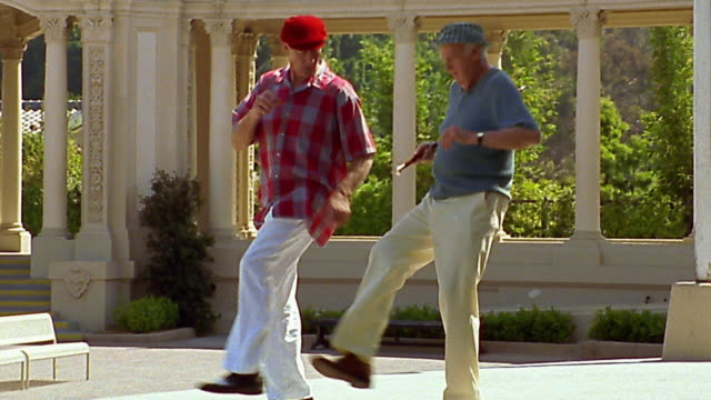 wide shot 2 senior men tap dancing in park - grandangolo tecnica fotografica video stock e b–roll