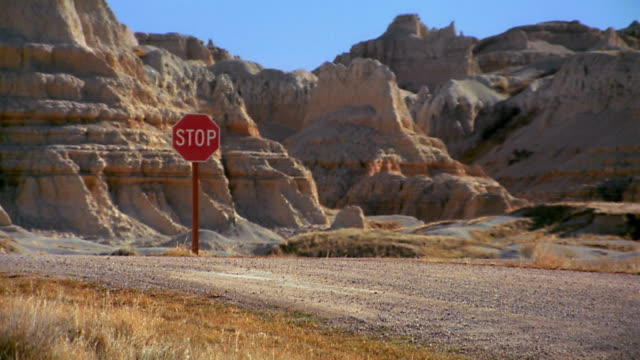 Wide shot 2 tumbleweeds rolling towards stop sign on desert road