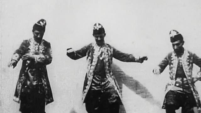 1895 wide shot 3 male dancers performing in costume at german vaudeville show - whatif点の映像素材/bロール