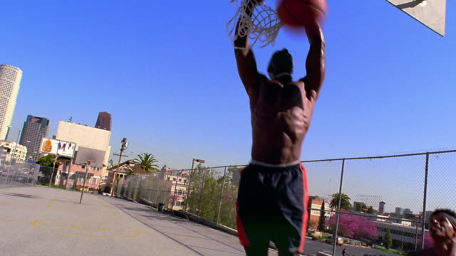 wide shot 4 Black men playing basketball, dunking, + posing to camera on outdoor court / Los Angeles