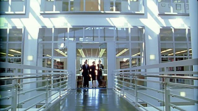 Wide shot 4 businesspeople walking out door and down hallway