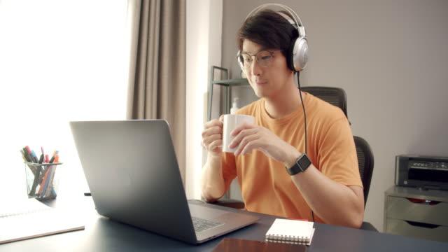 ワイドショット4k解像度アジア人男性は、ラップトップコンピュータ上で入力し、コロナウイルスやcovidロックダウン状況で自宅で働いている間にコーヒーカップを保持しています。リラクゼ - coffee cup点の映像素材/bロール