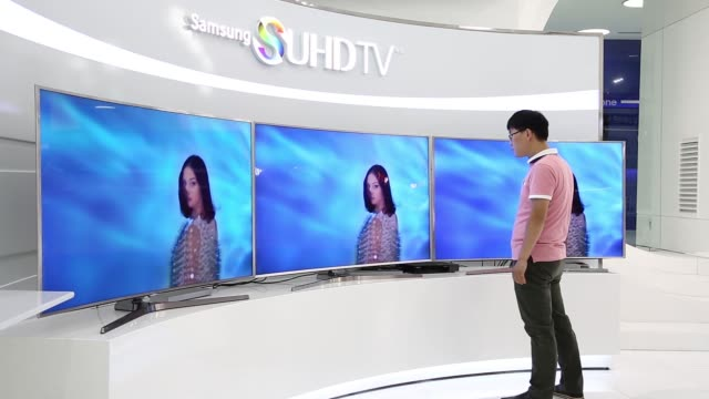 Wide shot a customer looks at Samsung Electronics Co SUHD 4K televisions on display at the company's Galaxy Zone showroom in Seoul