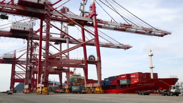 Wide shot a gantry crane unloads a shipping container from a docked ship at the Busan Port Terminal in Busan South Korea on Monday July 17 Medium...