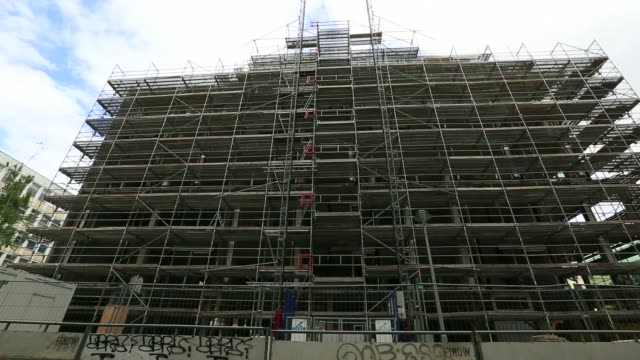 Wide shot a Hochtief AG logo sits on scaffolding surrounding a development of new residential apartments part of the Lux project operated by Ziegert...