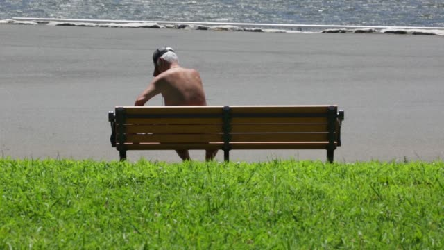 Wide shot a man lays on a lawn as he sunbathes topless in a park Wide shot men sit on benches as they sunbathe topless at a park Medium shot men sit...