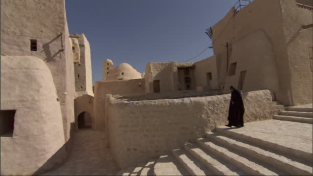 Wide Shot,  - A Muslim in traditional clothing walks down steps in an Egyptian town