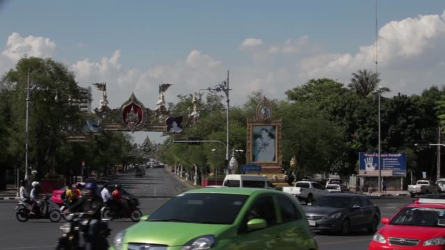 wide shot, a picture of thailand's queen is displayed on an overhead decoration as traffic passes below, wide shot, images of thailand's king and... - bangkok stock videos & royalty-free footage